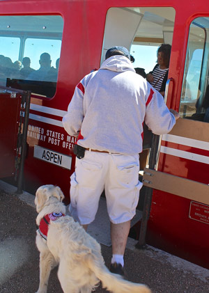 Cam'O, in his red Paw Pals I.D. jacket, boards the ASPEN Car on the Cog Railway for an adventure to new heights, 14,110 feet!