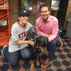 Colt, in a Tigers jersey, and Steve Sparks, wearing a pink shirt, kneel with Kaline in front of a case of baseballs at Comerica Park.
