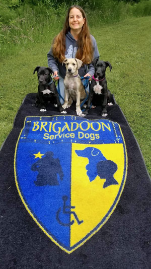 Amie poses with Bernard, Bianca and Penny next to the Brigadoon logo.