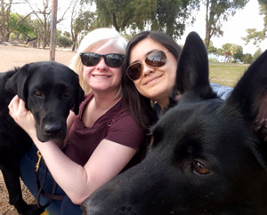 Kash and Gabrielle with their handlers, Trinda and Katie sitting in a park surrounded by trees.