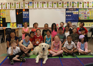Cam'o with a group of happy first graders (faces not visible to maintain privacy).