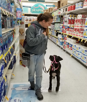 Penny and Amie walking down an aisle at the grocery store.