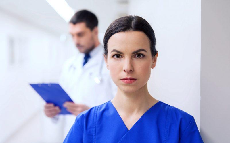 healthcare, profession, people and medicine concept - doctor or nurse at hospital corridor